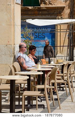 VALLETTA, MALTA - MARCH 30, 2017 - Couple sitting at a pavement cafe along Republic Street aka Triq Ir Repubblika Valletta Malta Europe, March 30, 2017.