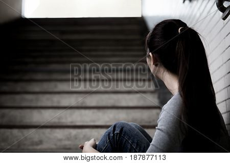 depressed woman sit and look somewhere in underground
