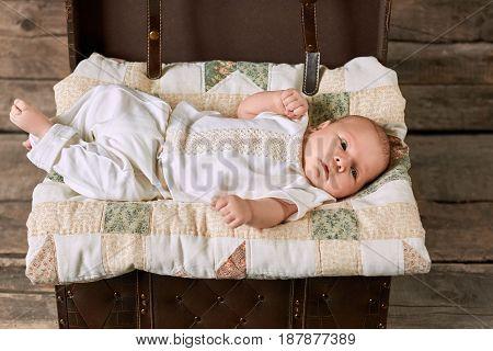 Baby boy lying on blanket. Open suitcase and little kid.