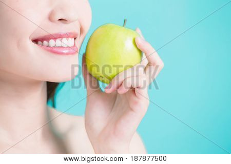 beauty woman take apple with health tooth on the green background