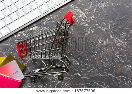 trolley, keyboard and credit cards for online purchasing on dark desk background top view mockup