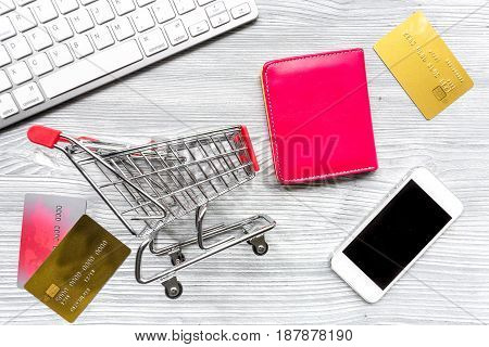 online purchasing with mini trolley, cards and phone on light office desk background top view mock up