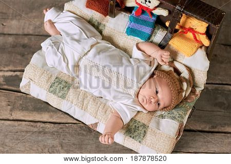 Suitcase with blanket and child. Infant boy in knitted hat.