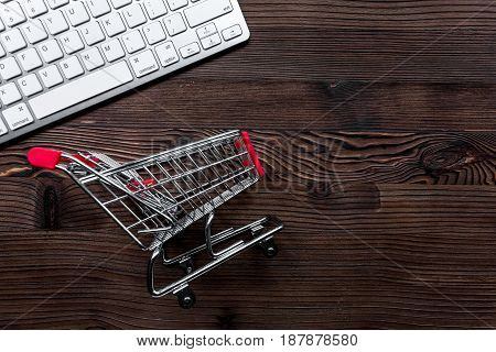 online purchasing with mini trolley on wooden office desk background top view mock up