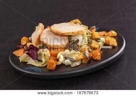 Caesar salad with sunflower seeds on dark black background. Culinary salad eating.