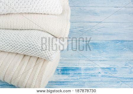 Knitted wool sweaters. Pile of knitted winter clothes on blue wooden background, sweaters, knitwear, space for text