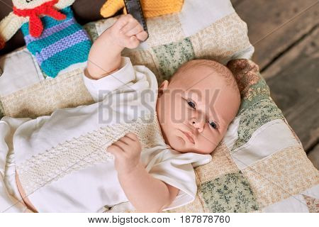 Cute caucasian baby boy. Child lying on a blanket.