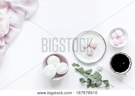 woman lunch with marsh-mallow, cup of coffee and flowers trendy design in soft light on white table background flat lay v