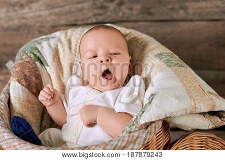 Baby is yawning. Infant with mouth open. Tiredness and boredom.