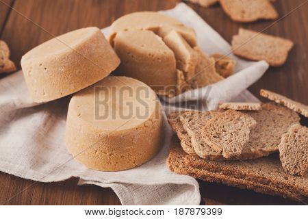 Norwegian homemade brown cheese brunost with crackers or crispbread on wooden desk, close-up, selective focus