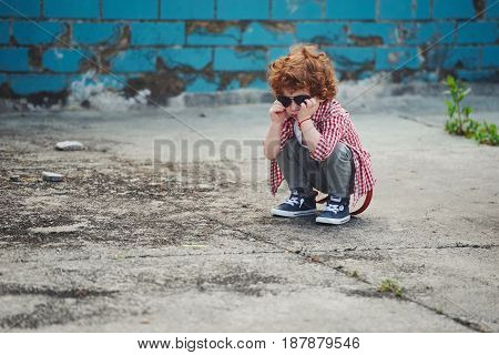 photo of cute little serious boy with sunglasses