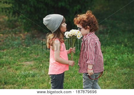 photo of two cute hipsters smell the flowers