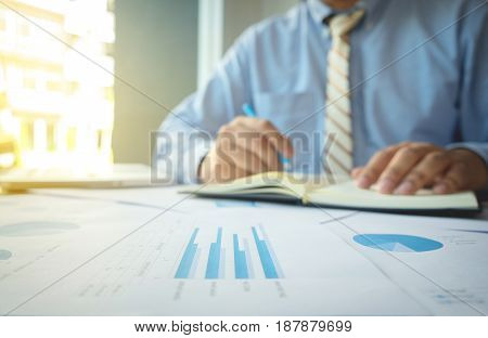 Young man working and writing in Book on his desk with financial grap document business person at workplace.
