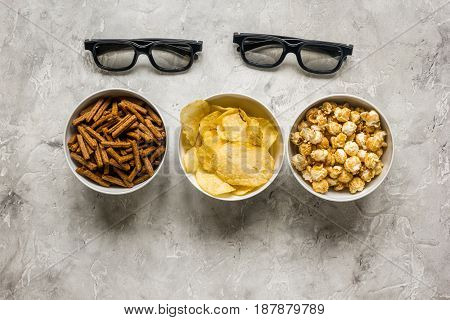 watching TV set with chips, pop corn and crumbs on stone table background top view