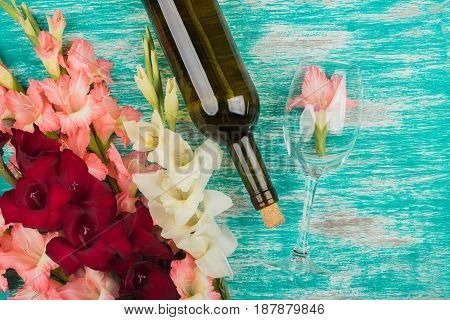Bottle Of Wine And Wineglass With Different Gladiolus On The Azure Background