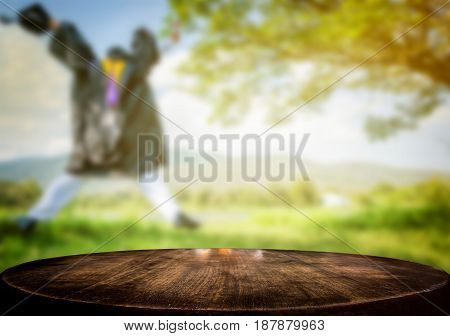 Selected focus empty brown wooden table and nature field or graduate man blur background image. for your photomontage or product display
