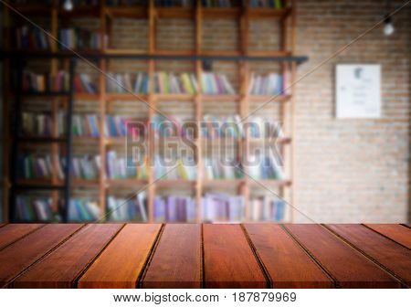Selected focus empty brown wooden table and Library or Bookstore blur background with bokeh image. for your photomontage or product display.