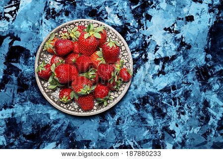 fresh ripe useful fruit strawberry in a clay bowl closeup on a marble dark blue background