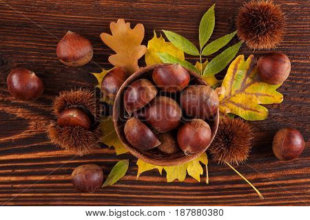 Chestnuts from above on wooden background with autumn leafs. Seasonal autumn background.