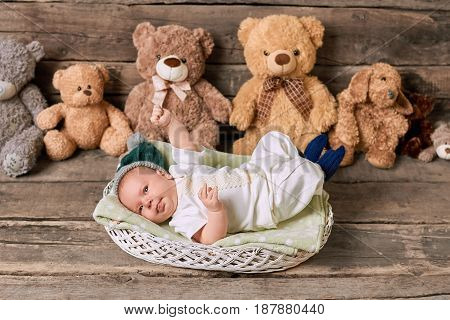 Basket, child and teddybears. Little kid on wooden background. Prepare home for a baby.