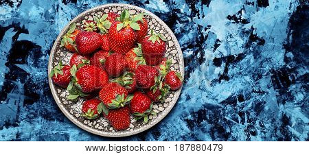 fresh ripe useful fruit strawberry in a clay bowl closeup on a marble dark blue background, border design panoramic banner