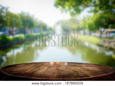 Selected focus empty wooden table and view of river nature blur background with bokeh image. for your photomontage or product display.