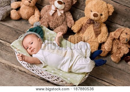 Basket and child, wooden background. Cute infant and teddybears.