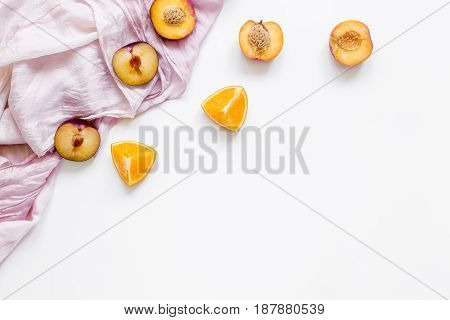 tropical peach and orange fruits for fresh summer juice with towel on white table background top view space for text