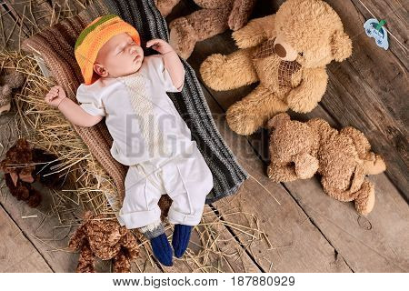 Sleeping kid on wooden background. Teddybears and child, top view.