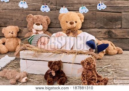 Teddybears and sleeping kid. Child lying on hay. How long should children sleep.