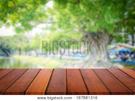Selected focus empty brown wooden table and green garden or forest blur background with bokeh image. for your photomontage or product display.