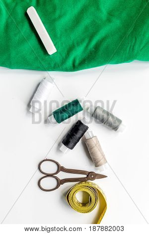sewing hobby with tools, thread, scissors white desk background top view