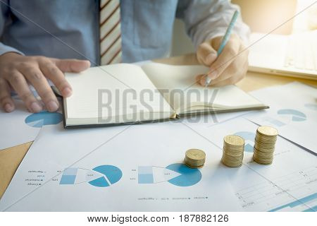 businessman writting note paper with stacked coins arranged at office desk and many document data graph in morning light business concept.