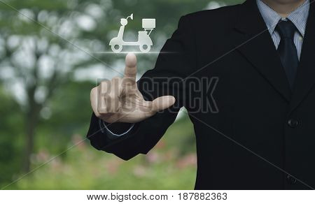 Businessman pressing motor bike icon over blur flower and tree in park Business delivery service concept