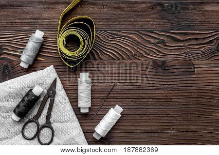 Sewing tools, fabric and kit for handmade hobby collection on wooden background top view mock-up