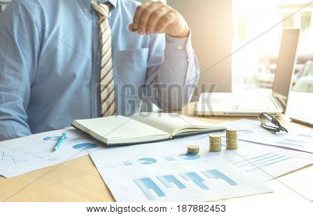 businessman pointing coins with stacked coins arranged at office desk and many document data graph in morning light business concept.