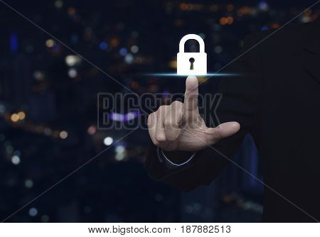 Businessman pressing key icon over blur colorful night light city tower Business security concept