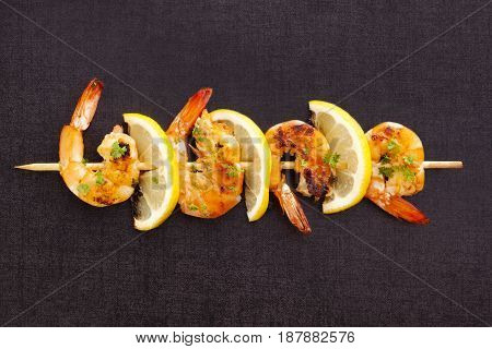 Grilled shrimps on skewer with lemons on dark concrete background. Culinary gourmet seafood eating.