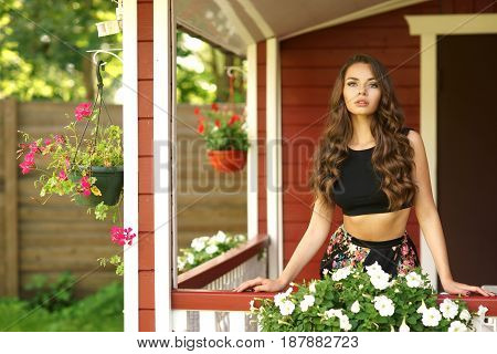 Beautiful girl at summer terrace in garden on a sunny day. Pretty young woman with long loose wavy hair. Blooming flowers. Happy joyous smiling lady.