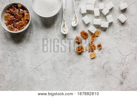 lumps of white and brown sugar on gray kitchen table background top view mock up