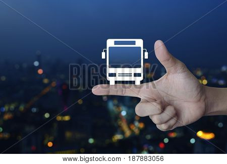 Bus flat icon on finger over blur colorful night light city tower Business transportation service concept