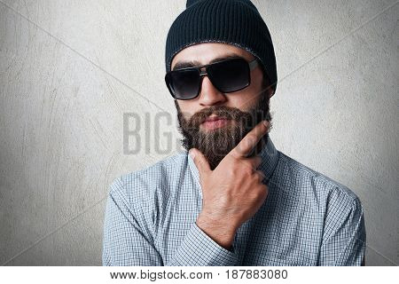 Close-up Portrait Of Handsome Bearded Man Wearing Stylish Black Cap, Checked Shirt And Sunglasses Ho