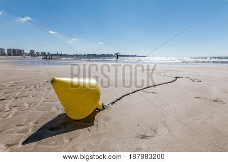 Yellow conical buoy on the beach of Les Sables d'Olonne at low tide