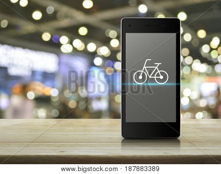 Bicycle flat icon on modern smart phone screen on wooden table over blur light and shadow of shopping mall Bike shop online concept