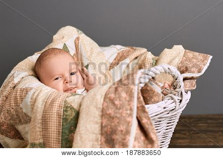 Kid in a basket. Caucasian baby and blanket.
