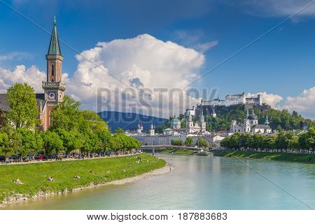Classic postcard view of the historic city of Salzburg with famous Festung Hohensalzburg reflecting in beautiful Salzach river in summer Salzburger Land Austria