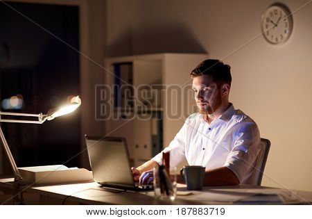 business, overwork, people, deadline and technology concept - businessman with laptop computer typing at night office