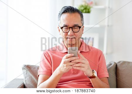 technology, people, lifestyle and communication concept - man with smartphone sitting on sofa at home