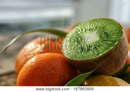 Different fresh citrus fruits with half of kiwi on top, closeup