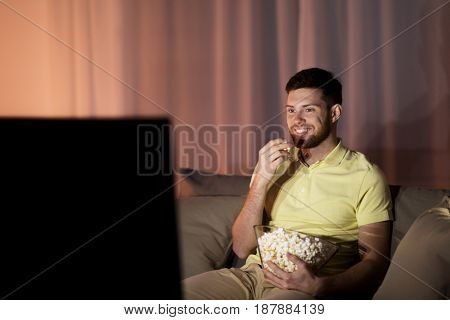 people, mass media, television and entertainment concept - happy smiling young man watching tv and eating popcorn at night at home